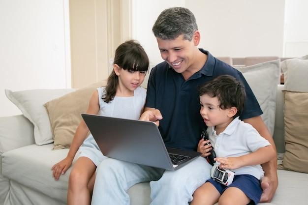 ノートパソコンのコンテンツを好奇心旺盛な2人の子供に見せている陽気なお父さん。家で映画を見ている家族。
