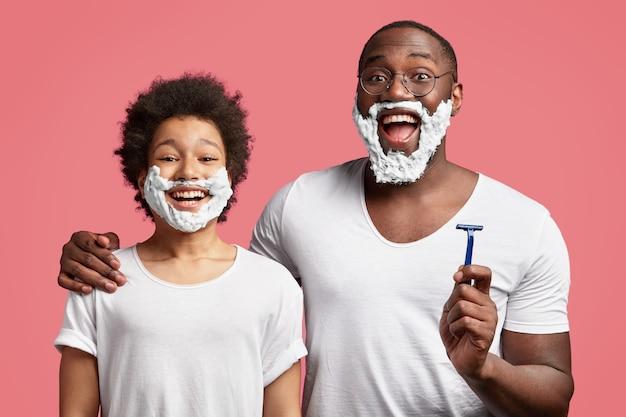 Papà e figlio allegri con gel da barba sulle guance, tengono in mano il rasoio, si abbracciano, vestiti con una maglietta bianca, hanno ampi sorrisi