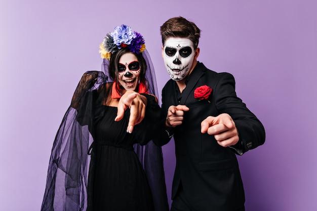 쾌활한 검은 머리 소년과 할로윈에 그려진 얼굴로 그의 여자 친구는 웃고 카메라에 손가락을 보이고 있습니다.