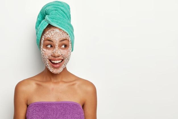 Allegro modello femminile dalla pelle scura indossa un asciugamano sulla testa e sul corpo, applica una maschera al sale marino per il peeling dai pori, guarda da parte con soddisfazione