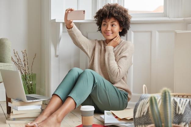 Веселая смуглая девушка носит теплый свитер и модные брюки.