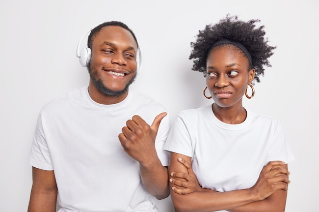 Cheerful dark skinned guy points at offended female friend