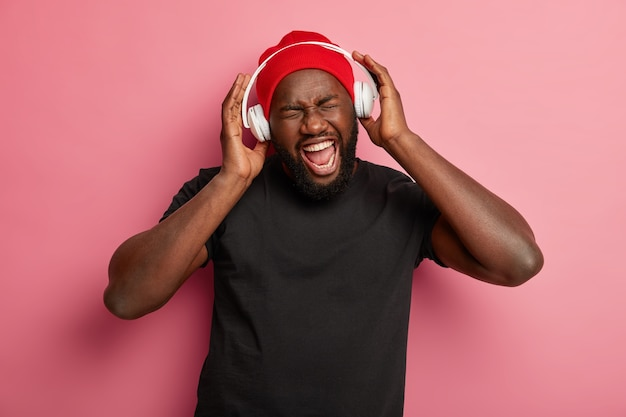 Cheerful dark skinned hipster man uses headphones for noise cancellation, listens rock music, sings song aloud, wears red hat and black t shirt.