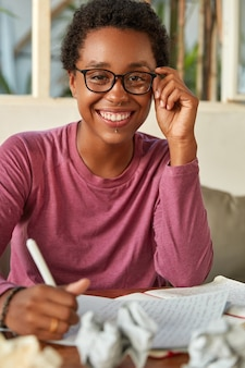 Cheerful dark skinned lady takes notes, creats reminder in calendar