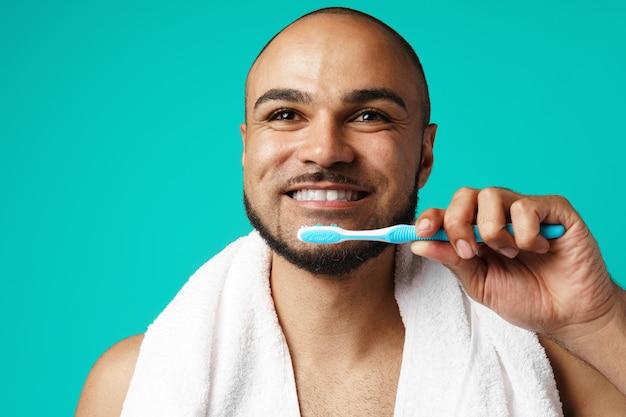 ターコイズブルーの背景に対して彼の歯を磨く陽気な浅黒い肌の男性