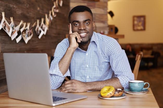昼休み中にカフェで残りの部分を持つ正式なシャツで陽気な浅黒い肌の男性