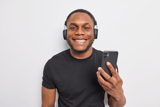 Cheerful dark skinned man smiles pleasantly enjoys listening to  music from playlist holds smartphone and uses wireless headphones