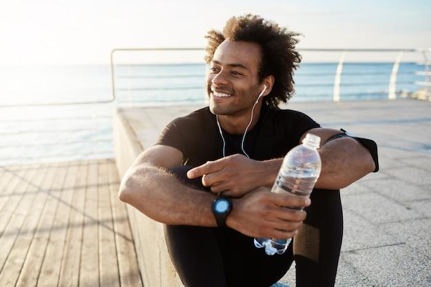 Cheerful dark-skinned muscular athlete in black sport clothing sitting on pier after sport activities wearing white earphones.