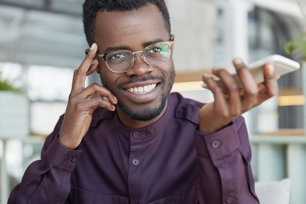 Cheerful dark skinned prosperous businessman in spectacles, has broad shining smile, holds smart phone and confirms banking in app