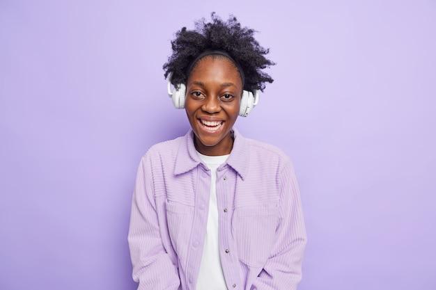 陽気な暗い肌の10代の少女の笑顔は楽しく音楽を聴いて楽しんでいます笑顔は歯ごたえのあるワイヤレスヘッドフォンを使用しています