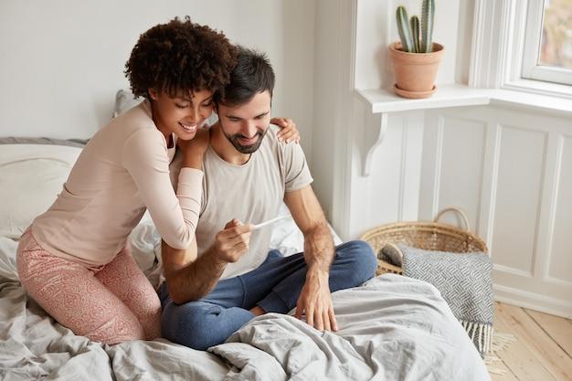 陽気な浅黒い肌の女性は夫を抱きしめ、テストで陽性の結果を示し、彼らがすぐに両親になることを喜んでいます、