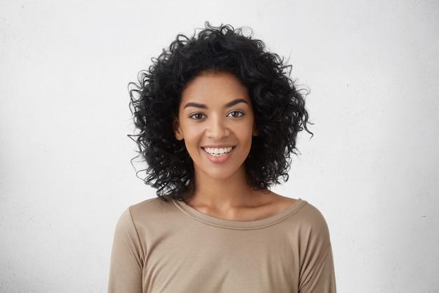 Allegra donna dalla pelle scura che sorride ampiamente, rallegrandosi per la sua vittoria in competizione tra giovani scrittori, in piedi isolato contro il muro grigio. concetto di persone, successo, gioventù e felicità