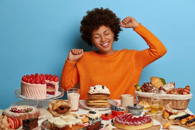 Веселая смуглая женщина протягивает руки, небрежно одета, сидит за столом с множеством вкусных тортов, десертов и пирогов, в хорошем настроении ест вкусную еду.