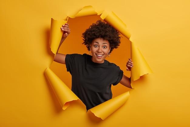 쾌활한 어두운 피부를 가진 여자는 검은 색 티셔츠를 입고 찢어진 종이 벽에 서서 행복을 표현합니다.