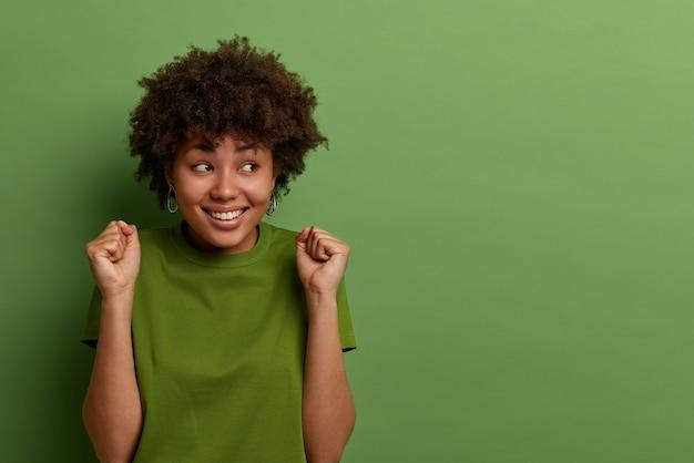 アフロの髪型、握りこぶしを握りしめ、肯定的な結果を待って、喜んで脇に見え、カジュアルな服装で身を包み、緑の壁に隔離され、広告用のスペースをコピーする陽気な暗い肌の女性