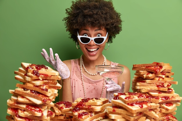 Cheerful dark skinned woman with curly hair, dressed in stylish clothes, wears sunglasses, drinks alcoholic cocktail, hears excellent news from interlocutor, stands near stack of sandwiches.