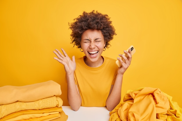 Cheerful dark skinned woman with curly hair gets excellent news holds mobile phone raises palm feels very happy sits at table near pile of unfolded laundry stack of folded clothes yellow wall