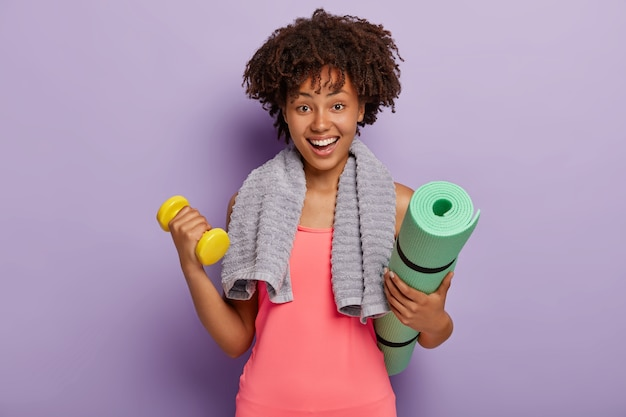 Cheerful dark skinned young afro woman holds mat and dumbbell, trains muscles in gym, has happy facial expression, towel around neck, wears pink top, models indoor against purple wall