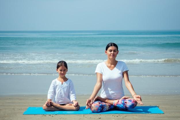 Веселая дочь и красивая мама вместе занимаются йогой и медитируют на пляже.