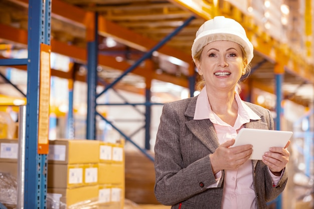 Cheerful delighted businesswoman smiling while holding a tablet