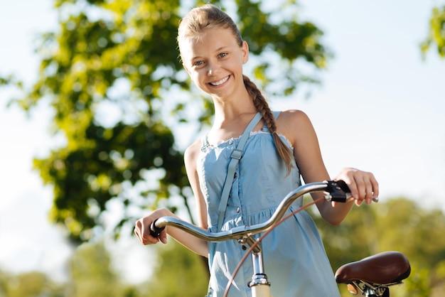 自転車を持って元気に喜んでいる少女