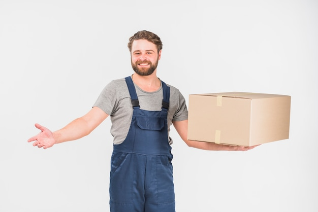 Cheerful delivery man standing with big box