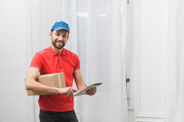 Cheerful delivery man with tablet and box