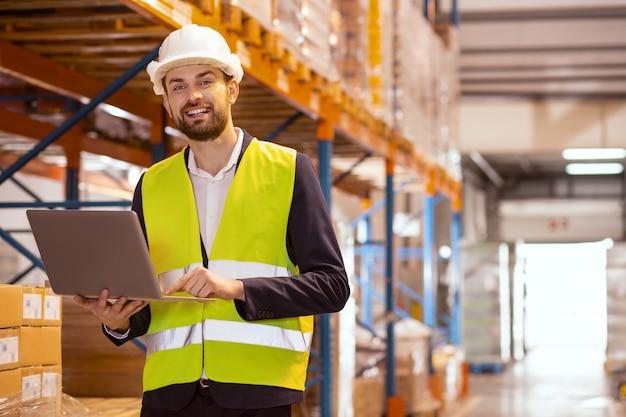 倉庫での作業を制御しながら彼のラップトップを保持している陽気な配達マネージャー