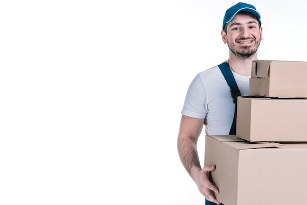 Cheerful deliveryman carrying stack of parcels