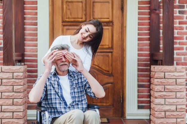 彼の幸せな孫娘を歓迎する車椅子の陽気な障害者の祖父