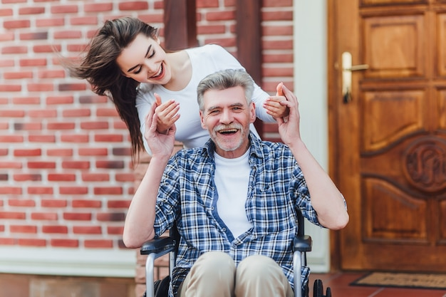 Cheerful disabled grandfather in wheelchair welcoming his happy granddaughter  near nursing home