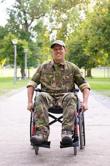 迷彩服を着て、都市公園の歩道を移動している車椅子の陽気な障害のある軍人。正面図。戦争または障害の概念のベテラン