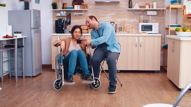 휠체어를 탄 쾌활한 장애인 여성이 부엌에서 남편과 셀카를 찍고 있습니다. 장애인 장애를 가진 희망적인 남편 옆에 있는 무효 마비 장애인
