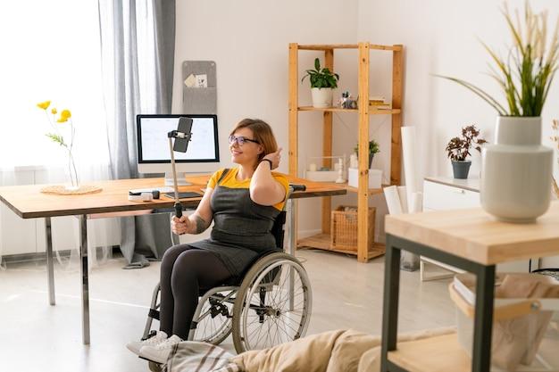 Веселая молодая женщина-блогер-инвалид в очках сидит в инвалидной коляске и транслирует потоковое видео