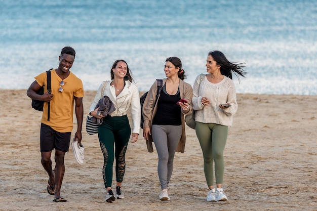 Cheerful diverse friends walking on beach together