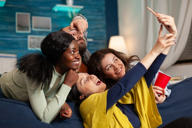 Cheerful diverse groupg of friends taking selfie photos having fun, drinking beer, sitting on couch socialising. multhiethnic peple posting picturez on internet sharing with other person.