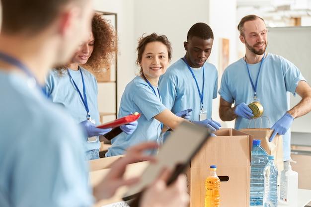함께 일하는 판지 상자에 음식을 분류하는 동안 웃고 있는 쾌활한 다양한 자원 봉사자