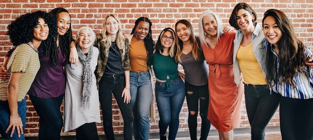 Cheerful diverse women standing in front of a red brick wall