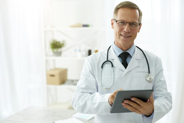 Cheerful doctor in lab coat using tablet computer in clinic