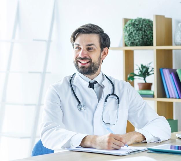 Веселый доктор делает заметки и смотрит в сторону