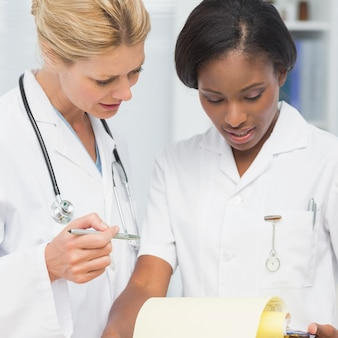 Cheerful doctor and nurse going over file together in an office at the hospital