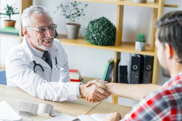 Cheerful doctor shaking hand of patient