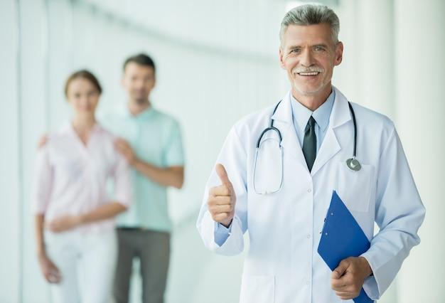 Жизнерадостный доктор стоя на клинике и усмехаясь на камере.