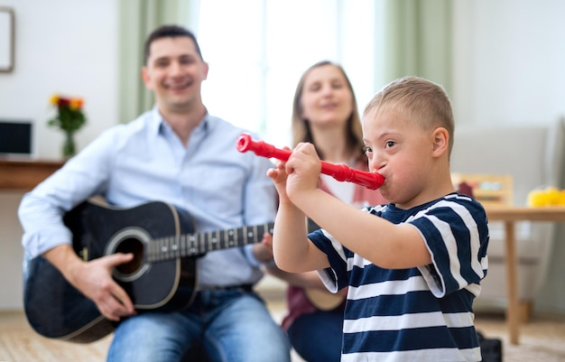 A cheerful down syndrome boy with parents playing musical instruments, laughing.