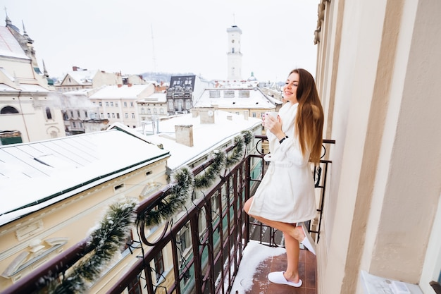 Cheerful dreaming woman in a white robe, standing on the balcony and holding a cup of tea or coffee and looking at the city.