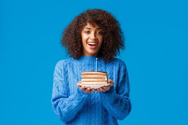 Allegra e sognante ragazza carina afro-americana b-day, che tiene la torta con la candela, che spegne e che sorride, avendo festa di compleanno, in piedi nel muro blu del maglione.