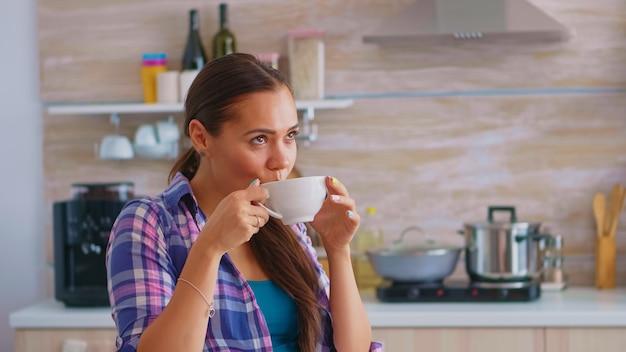 Веселая мечтательная дама пьет горячий зеленый чай по утрам. женщина, имеющая отличное утро, пьет вкусный натуральный травяной чай, сидя на кухне во время завтрака, расслабляясь, держа чашку.