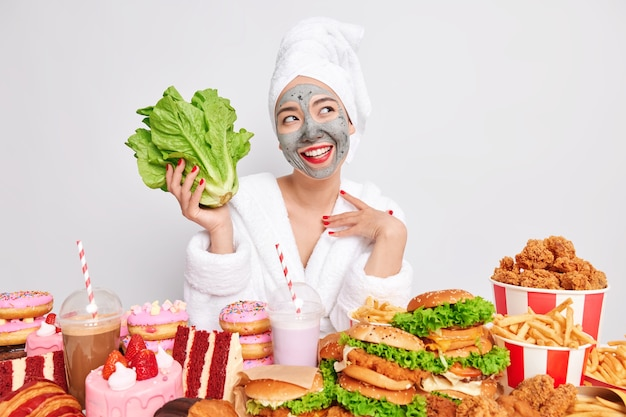 Cheerful dreamy young woman undergoes beauty procedures at home looks happily away holds green romaine lettuce