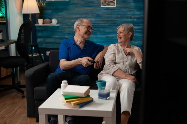 Веселые пожилые люди улыбаются, сидя на диване