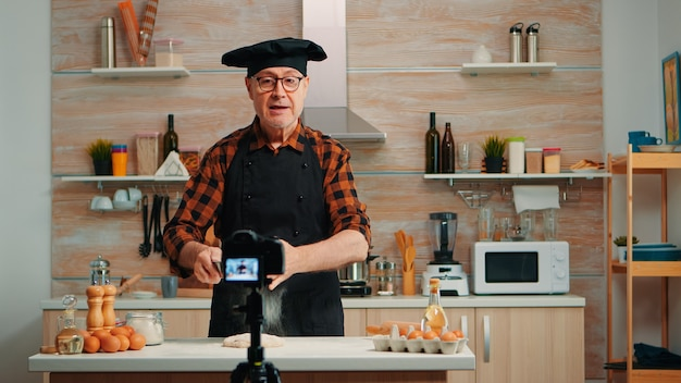 Cheerful elderly baker man filming cooking vlog in home kitchen. retired blogger chef influencer using internet technology communicating, shooting blogging on social media with digital equipment